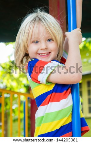 Cute smiling child playing on a pole in a play ground - stock photo
