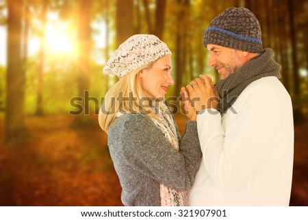 Cute smiling couple holding hands against autumn scene