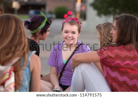 Cute smiling female student in purple sitting among friends - stock photo