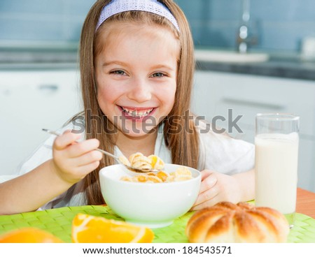 cute smiling girl eating cereal with the milk in the kitchen - stock photo