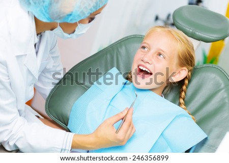 Cute smiling girl in at dentist sitting in armchair - stock photo