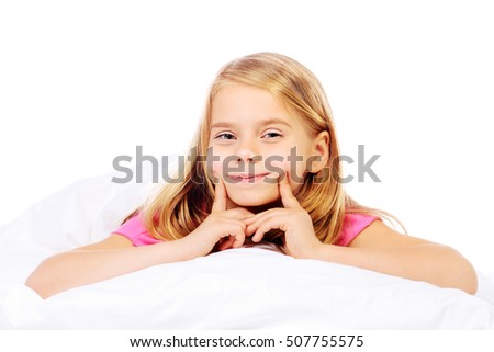 Cute smiling girl in her bed in the nursery. Healthcare, beauty.