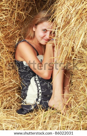 cute smiling girl in sarafan sit between straw bales