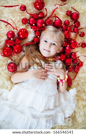 cute smiling girl lies on the fur around her red Christmas balls - stock photo