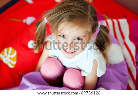 Cute smiling girl on the bed - stock photo