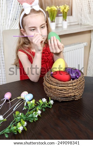 Cute  smiling girl painting easter egg - stock photo