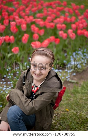 Cute Smiling Girl sitting in Spring Tulips  - stock photo