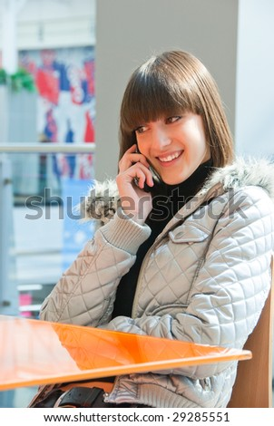 Cute smiling girl speaks on a mobile phone