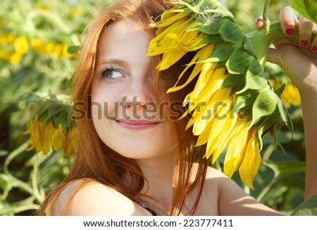 Cute smiling girl with a sunflower. The sunflower field, summertime
