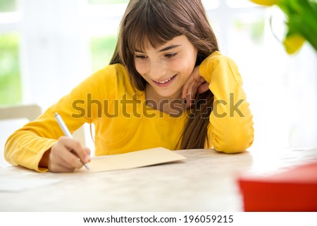 Cute smiling girl writing a letter sitting at desk