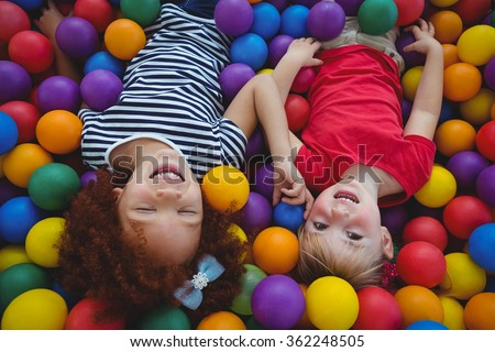 Cute smiling girls in sponge ball pool looking at the camera - stock photo
