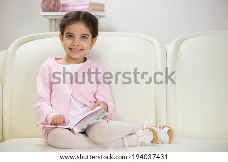 Cute smiling hispanic girl sitting on sofa with book - stock photo
