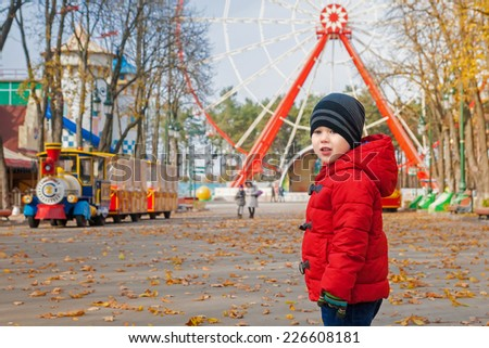 Cute smiling kid outdoors on playground in autumn - stock photo