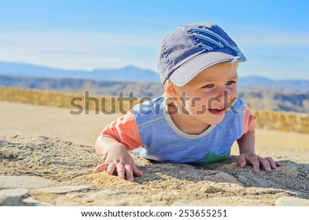 Cute smiling little boy laying down on the rock - stock photo