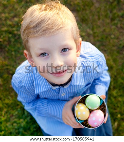 cute smiling little boy looking up and holding bucket with colorful eggs at easter time
