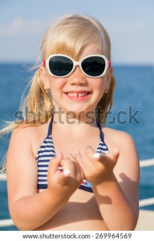 Cute smiling little girl anoints her face protective cream on the beach - stock photo