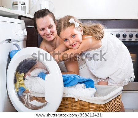 Cute smiling little girl helping mom to load washing machine 
