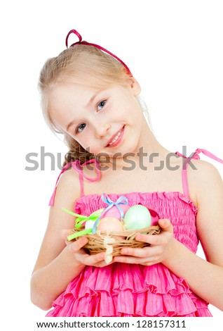 cute smiling little girl holding Easter eggs in basket - stock photo