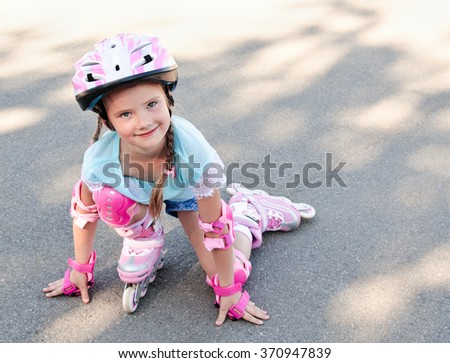 Cute smiling little girl in pink roller skates and protective gear outdoor
