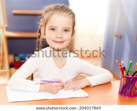Cute smiling little girl is writing at the desk  in preschool