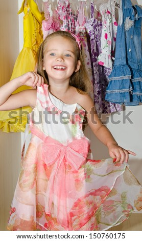 Cute smiling little girl measures a dress from the wardrobe