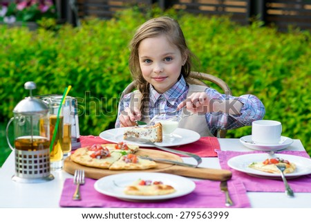 cute smiling little girl sitting by dinner table and eating cake. Kid eats healthy food. Fine dinning. - stock photo