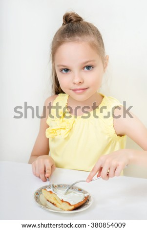 Cute smiling little girl sitting by dinner table and eating. Kid eats healthy food. Fine dinning. - stock photo