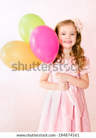 Cute smiling little girl with balloons in princess dress - stock photo