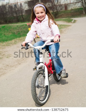 Cute smiling little girl with bicycle on road - stock photo