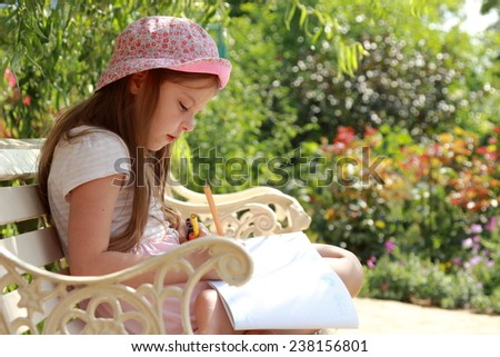 Cute smiling little girl with enthusiasm draws in album sitting in the summer park bench - stock photo
