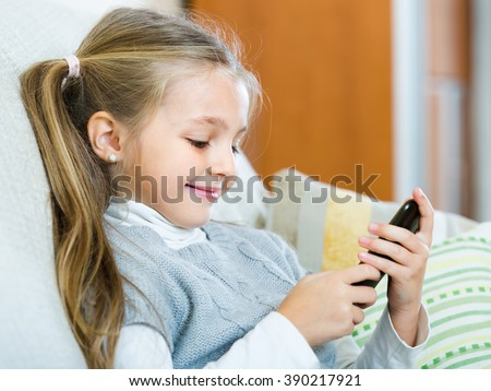 Cute smiling little girl with long hair having fun with cell phone at home