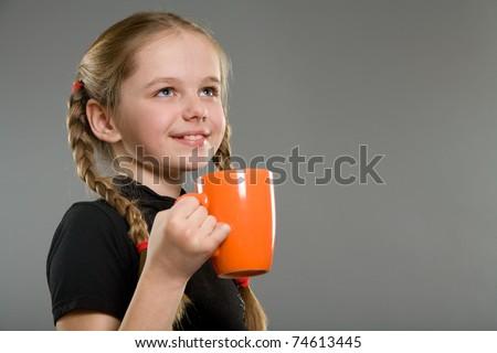 Cute smiling little girl with orange mug - stock photo