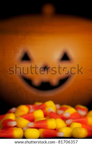Cute, Smiling Pumpkin Overlooking a Pile of Candy Corn in a Spooky Setting - stock photo