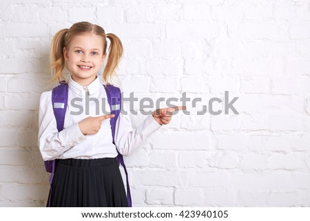 Cute smiling schoolgirl in uniform standing on light  background and showing  thumbs to the side. Copy space - stock photo