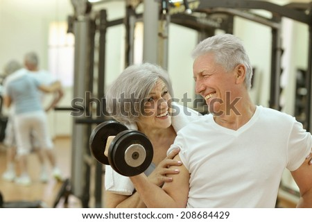 Cute smiling senior couple exercising in gym - stock photo