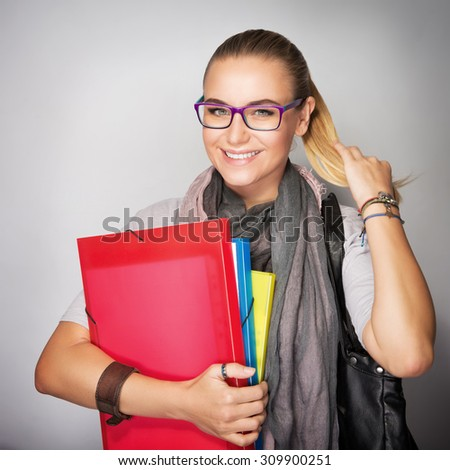 Cute smiling student girl with colorful folders in hands posing in the studio over gray background, back to school