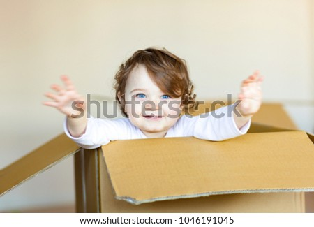 Cute smiling toddler baby girl sitting inside brown cardboard box.