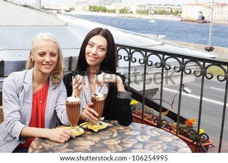 cute smiling women drinking a coffee sitting outside in a cafe bistro - stock photo