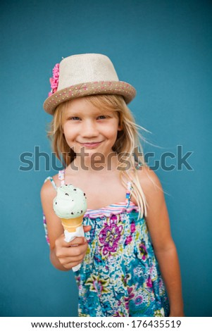 Cute smiling young girl holding ice cream cone outside against blue wall background - stock photo