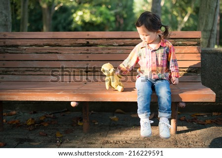Cute Smiling Young Girl Hugging Her Teddy Bear on Bench Outside - stock photo
