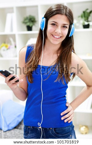 Cute, smiling, young teenage girl standing and listening to music with headphones - stock photo