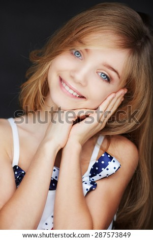 Cute smilling girl with blue eyes. Isolated on dark background. - stock photo