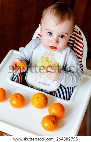 Cute smudgy baby with mandarines - stock photo