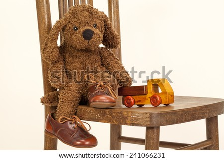 Cute Soft toy puppy sitting on a chair in old leather shoes - stock photo