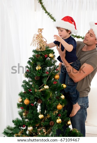Cute son decorating the christmas tree with his father in the living room - stock photo