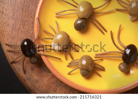 Cute spooky Halloween spider appetizers made from green, black and stuffed olives with spaghetti legs crawling off a yellow platter onto a wooden table, view from above - stock photo