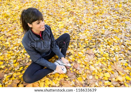 Cute sportswoman training and stretching legs and abductor muscles sitting on autumn golden leaves outside. - stock photo