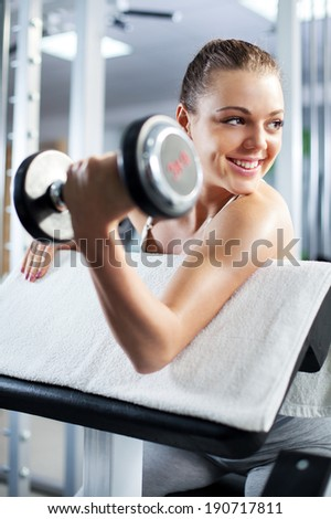 Cute Sporty young woman doing exercise in a fitness center. She is working exercises to strengthen her bicep.