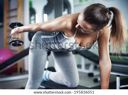 Cute Sporty young woman doing exercise in a fitness center. She is working exercises to strengthen her triceps. - stock photo