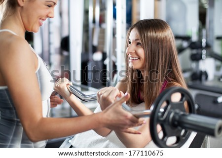Cute Sporty young woman doing exercise in a fitness center with her personal coach. She is working exercises to strengthen her bicep. - stock photo